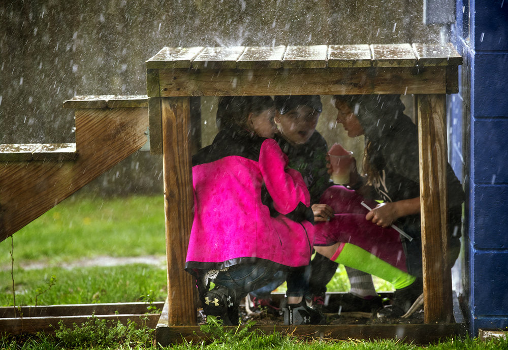Three girls take shelter from a downpour underneath a small stoop near the press box during the Williamsville versus Tri-City softball game Monday, April 10, 2017. Although the rain stopped, the game was called off due to wet field conditions. [Ted Schurter/The State Journal-Register]