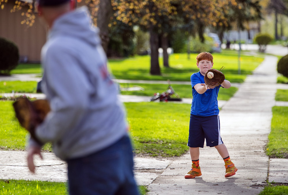 Jorey Myren eyes a throw all the way to the mitt as he plays catch with his dad Justin in front of their Springfield home Tuesday, April 11, 2017. Mryen, who had just wrapped up batting practice in the backyard, is the youngest of four baseball playing brothers. [Ted Schurter/The State Journal-Register]