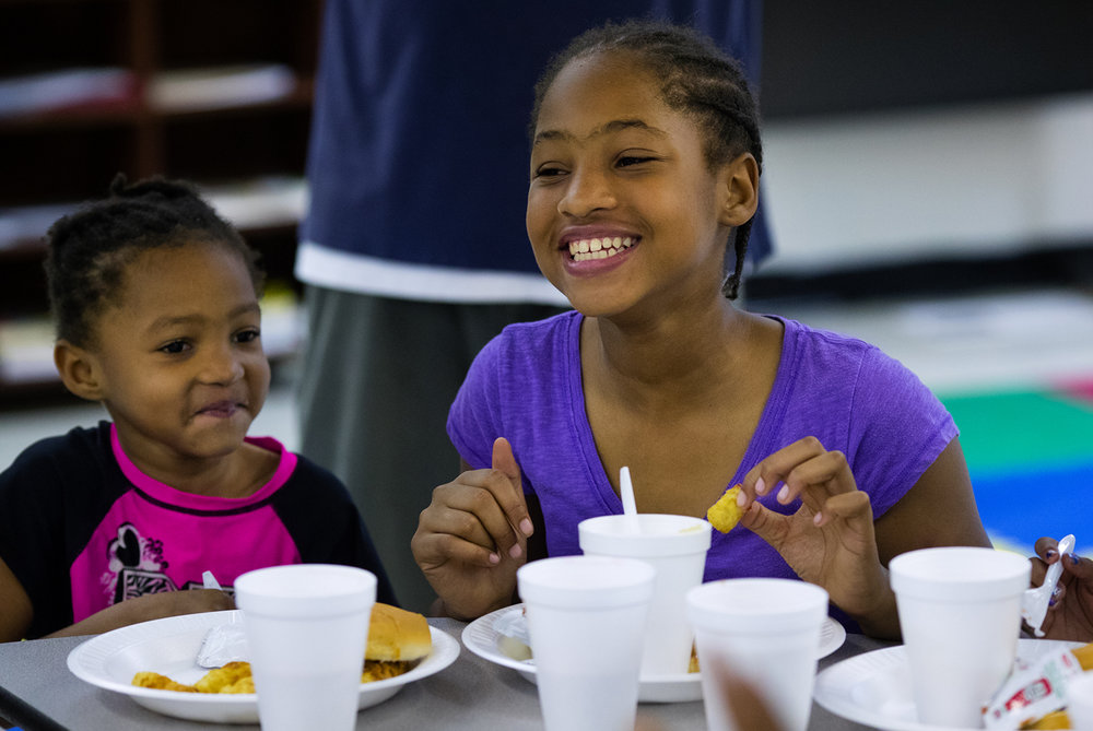 Jameia, and La'Myaha Ware eat lunch at the Brandon Outreach Center in Brandon Court Thursday, April 13, 2017. After art time, students at the center received a hot lunch provided by Nelson's Catering that was sponsored by Illinois National Bank employees. The lunches, offered Monday through Thursday for kids 17 and younger, coincided with the Central Illinois Foodbank's Kids Café, an after-school meal program and summer food service it operates at Brandon Outreach Center. [Ted Schurter/The State Journal-Register]