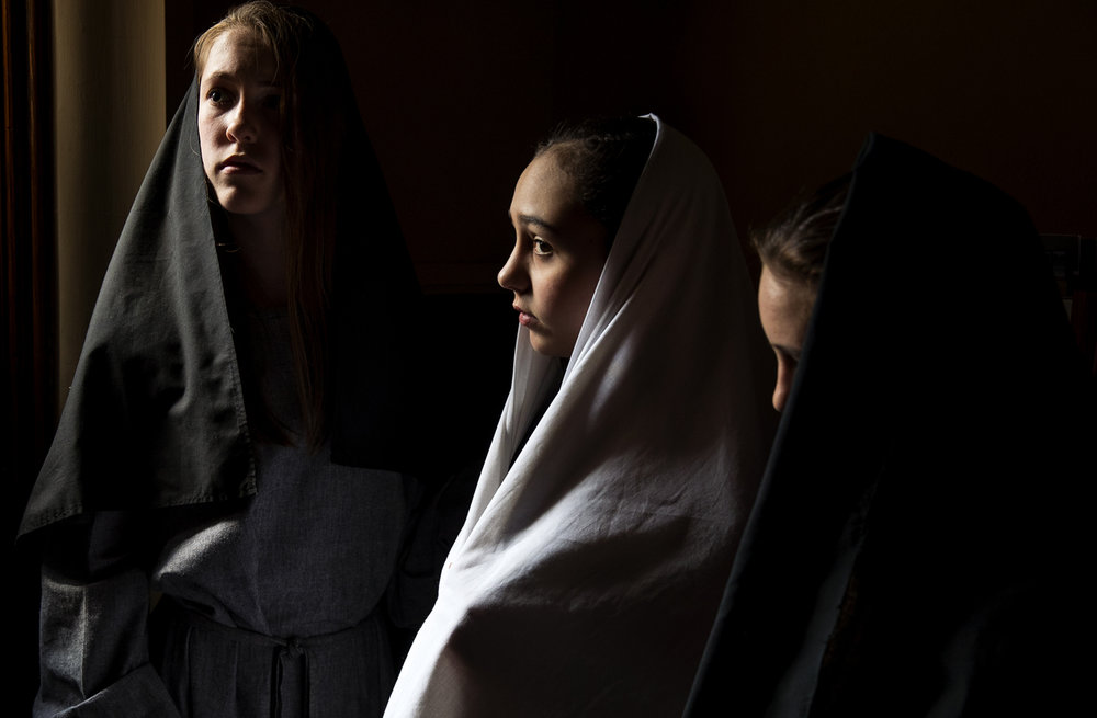 "Friends Audrey Frost, left, and Lucy Harvey, right, surround Mary, portrayed by Amelia Curtis, center, as they wait in the wings for their entrance in ""The Living Stations of the Cross"" presented by seventh graders at Blessed Sacrament Catholic Church Friday, April 14, 2017. [Ted Schurter/The State Journal-Register]"