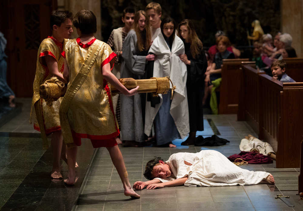 "Roman soldiers portrayed by Xander Eberding, left, and Griffin Cook carry away the cross after Jesus, portrayed by Spencer Wood, falls for the third time during ""The Living Stations of the Cross"" presented by seventh graders at Blessed Sacrament Catholic Church Friday, April 14, 2017. The presentation was to commemorate Good Friday, the day Christians observe the Friday before Easter when Jesus Christ was crucified.  [Ted Schurter/The State Journal-Register]"