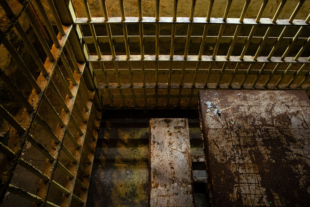 The common area of the 1869 Macoupin County Jail, known as the Cannonball Jail, in Carlinville, Ill., included a single table that crowded close to the edge of the cell block walls. Route 66 preservation groups have joined local efforts to restore and reopen the jail. [Ted Schurter/The State Journal-Register]
