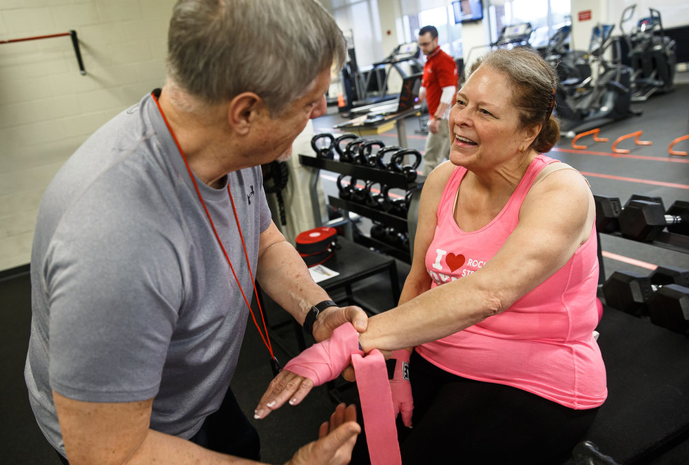 Lynn Kearney, right, gets help with her hand wraps from volunteer Alex Ferguson, left, in preparation for the Memorial Sportscare's Rock Steady Boxing program at the Kerasotes YMCA, Friday, April 14, 2017, in Springfield, Ill. The boxing program is geared towards helping those with Parkinson's which causes deterioration of motor skills, balance, speech and sensory function. [Justin L. Fowler/The State Journal-Register]