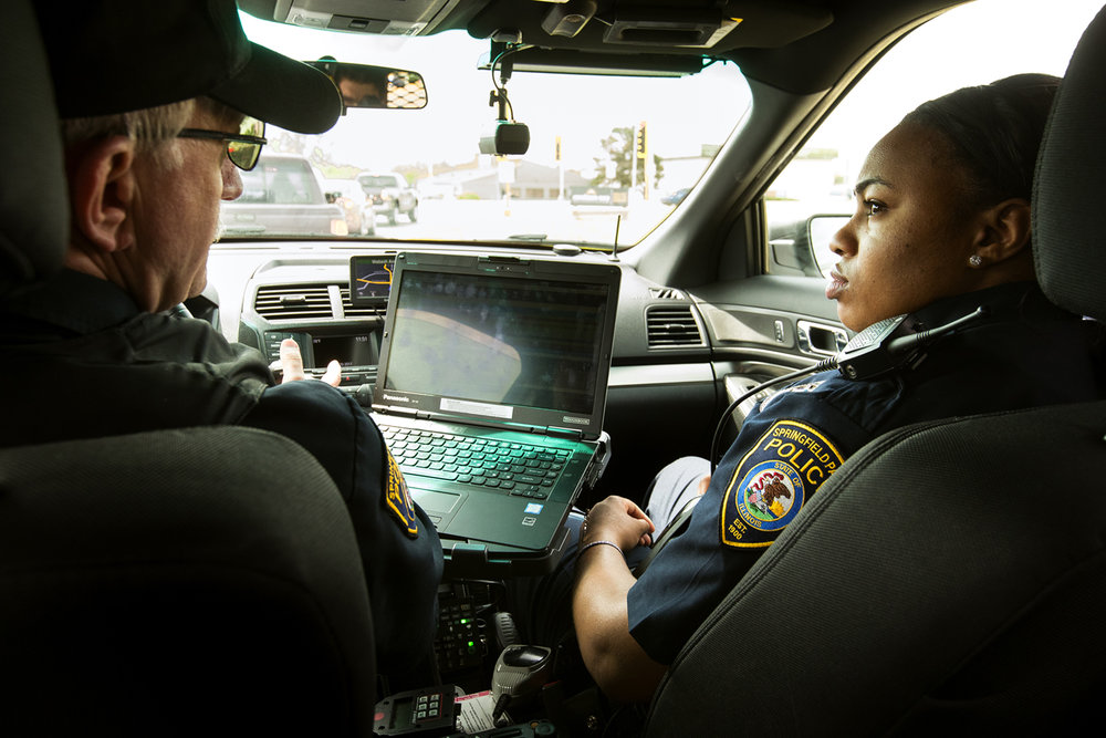 Part-time Springfield Park District Police Officer Brittany Rush listens to Officer Bill Piester they drive to Centennial Park at the start of Rush's shift Thursday, April 20, 2017. Rush is one of eight part time and four full time officers that cover 34 parks, four golf courses, two baseball fields, Henson Robinson Zoo and the Nelson Center. [Ted Schurter/The State Journal-Register]
