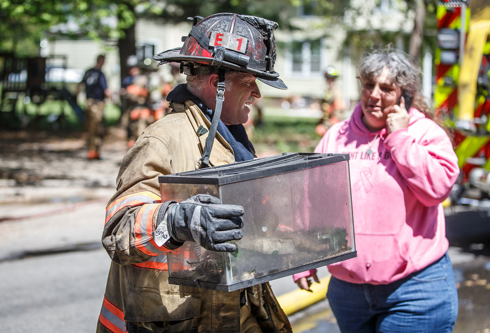 "Capt. Gene Powell, of the Springfield Fire Dept., carries out an aquarium containing a tarantula spider named ""Tess"" rescued from a structure fire that heavily damaged a home at 565 W. Elliot Ave., Sunday, April 23, 2017, in Springfield, Ill. The 14-year-old spider belonged to homeowner Christal Jackson, right, and was given to her by her late father. [Justin L. Fowler/The State Journal-Register]"