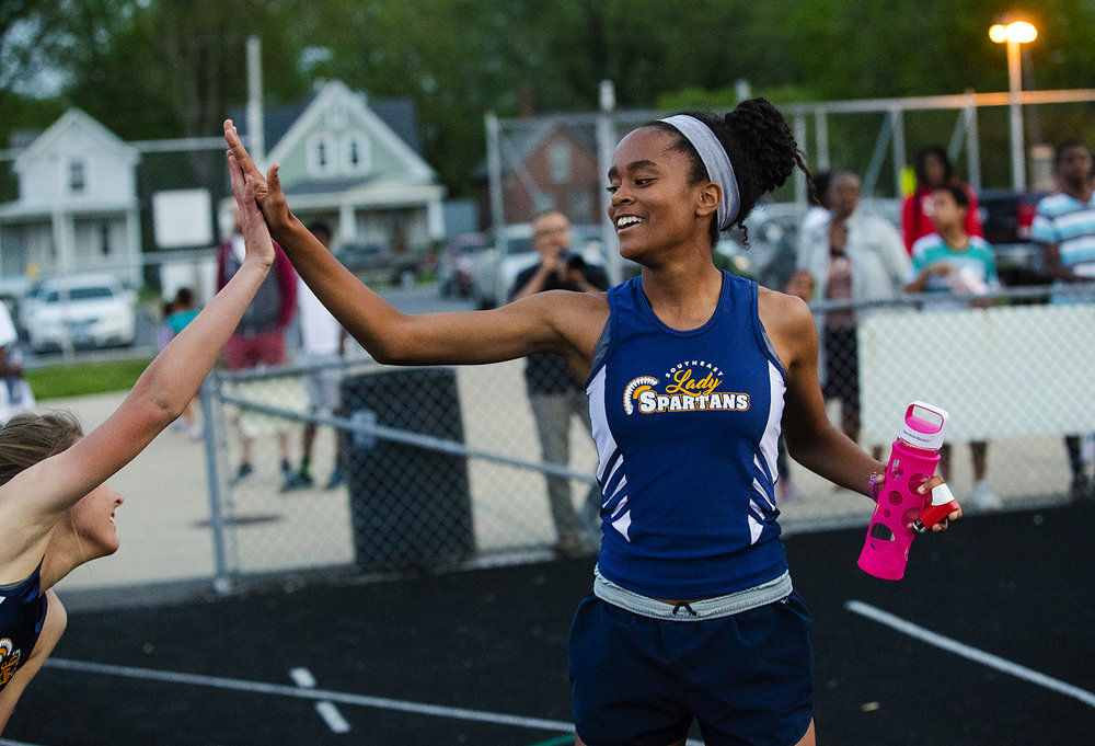 Southeast's Sydney Huffman high fives a teammate after winning the 1600 meter run during the Girls City Meet at Memorial Stadium Tuesday, April 25, 2017.  [Ted Schurter/The State Journal-Register]
