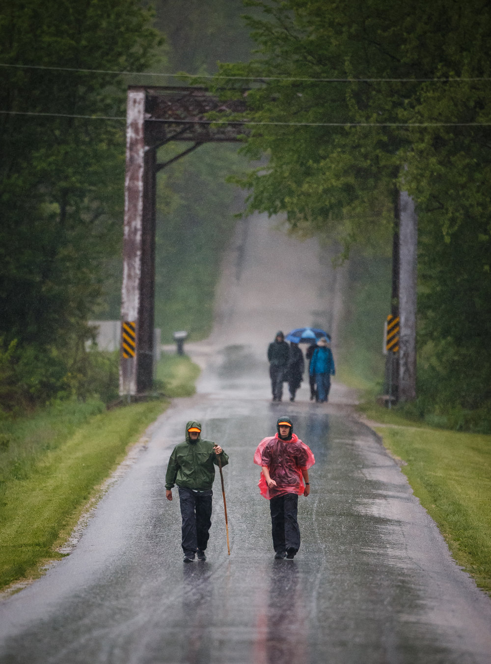 David Dempsey, left, and his son David Dempsey Jr., right, both of Edwardsville, Ill., and members of Troop 1072, make their way along the Lincoln Trail for the first time in pouring rain during the Lincoln Trail Hike, Saturday, April 29, 2017, north of Springfield, Ill. The 19-mile hike takes Boy Scouts from New Salem Historic Site to Stuart Park in Springfield.  [Justin L. Fowler/The State Journal-Register]