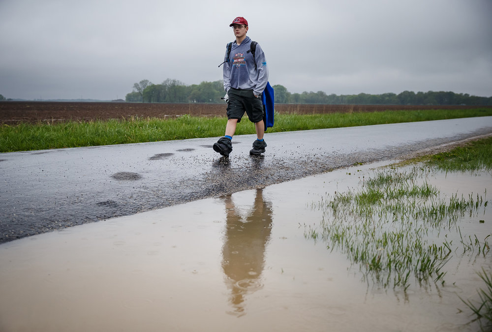 Kyle Haschemeyer, a member of Troop 210 out of Springfield, Ill., walks a portion of the Lincoln Trail without his poncho on with a break in the rain during the Lincoln Trail Hike, Saturday, April 29, 2017, north of Springfield, Ill.  The 19-mile hike takes Boy Scouts from New Salem Historic Site to Stuart Park in Springfield. [Justin L. Fowler/The State Journal-Register]