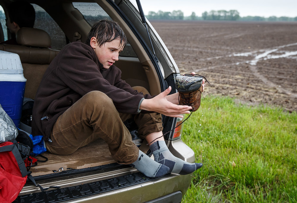 Daryk Baker, of Petersburg, Ill., and a member of Troop 54, dumps the water out of his boots as he stops with fellow Boy Scouts for a fresh pair of socks with five more miles to go during the Lincoln Trail Hike, Saturday, April 29, 2017, north of Springfield, Ill. The 19-mile hike takes Boy Scouts from New Salem Historic Site to Stuart Park in Springfield. [Justin L. Fowler/The State Journal-Register]