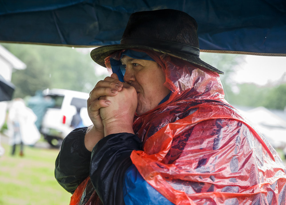 James Hubbard, of Bowen, Ill., with Troop 32, tries to keep his hands warm underneath a tent and out of the pouring rain during the Lincoln Trail Hike, Saturday, April 29, 2017, in Salisbury, Ill. The 19-mile hike takes Boy Scouts from New Salem Historic Site to Stuart Park in Springfield. [Justin L. Fowler/The State Journal-Register]