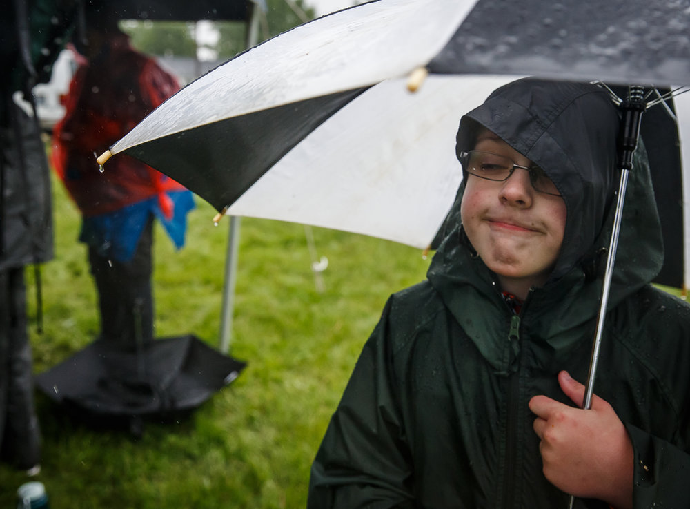 Evan Atterberry, of East Peoria, Ill., with Troop 627, makes the best of the situation as he stays underneath an umbrella as he and his fellow Boy Scouts seek refuge from the rain at a rest stop during the Lincoln Trail Hike, Saturday, April 29, 2017, in Salisbury, Ill. The 19-mile hike takes Boy Scouts from New Salem Historic Site to Stuart Park in Springfield. [Justin L. Fowler/The State Journal-Register]
