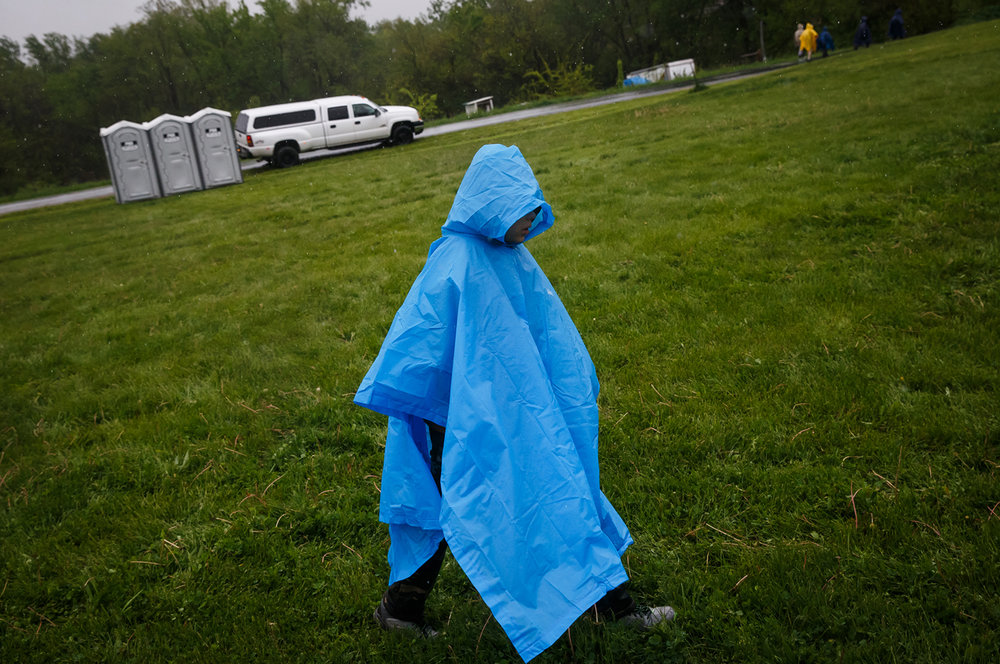 Damon Coller, of Mahomet, Ill., with Troop 103, seeks refuge from the rain underneath his poncho at a rest stop during the Lincoln Trail Hike, Saturday, April 29, 2017, in Salisbury, Ill. The 19-mile hike takes Boy Scouts from New Salem Historic Site to Stuart Park in Springfield. [Justin L. Fowler/The State Journal-Register]