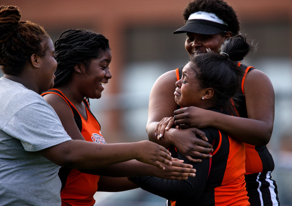 Velencia Johnson's Lanpheir teammates surround her as she breaks down in tears after learning her distance in the discuss, 104-09, was her personal best of the season and good for first place during the Girls City Meet at Memorial Stadium Tuesday, April 25, 2017.  [Ted Schurter/The State Journal-Register]