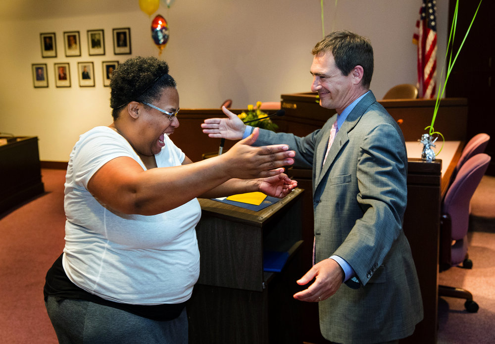 "Christine Overton hugs Sangamon County Circuit Judge John ""Mo"" Madonia during the first graduation ceremony for the mental health recovery court in the Sangamon County boardroom Friday, April 28, 2017. The court program aims to reduce recidivism and keeps defendants who might otherwise go to jail or prison on probation for two years as long as they attend therapy sessions and follow the program's guidelines. [Ted Schurter/The State Journal-Register]"