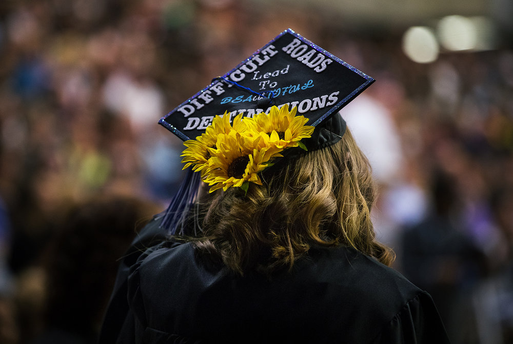 A University of Illinois Springfield graduate returns to her seat with flowers on her cap during commencement ceremonies for the College of Liberal Arts and Sciences at the Prairie Capital Convention Center Saturday, May 13, 2017. [Ted Schurter/The State Journal-Register]