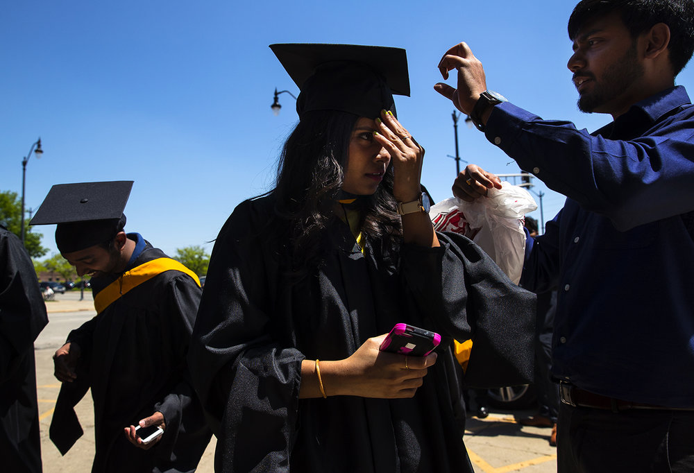 Poojitha Polusani tilts her head down as Vid Dau as helps adjust her cap before commencement ceremonies for the College of Liberal Arts and Sciences at the Prairie Capital Convention Center Saturday, May 13, 2017. [Ted Schurter/The State Journal-Register]
