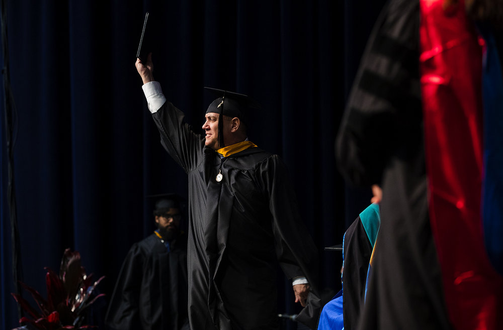 A University of Illinois Springfield graduate holds up his diploma case as he walks across stage during commencement ceremonies for the College of Liberal Arts and Sciences at the Prairie Capital Convention Center Saturday, May 13, 2017. [Ted Schurter/The State Journal-Register]