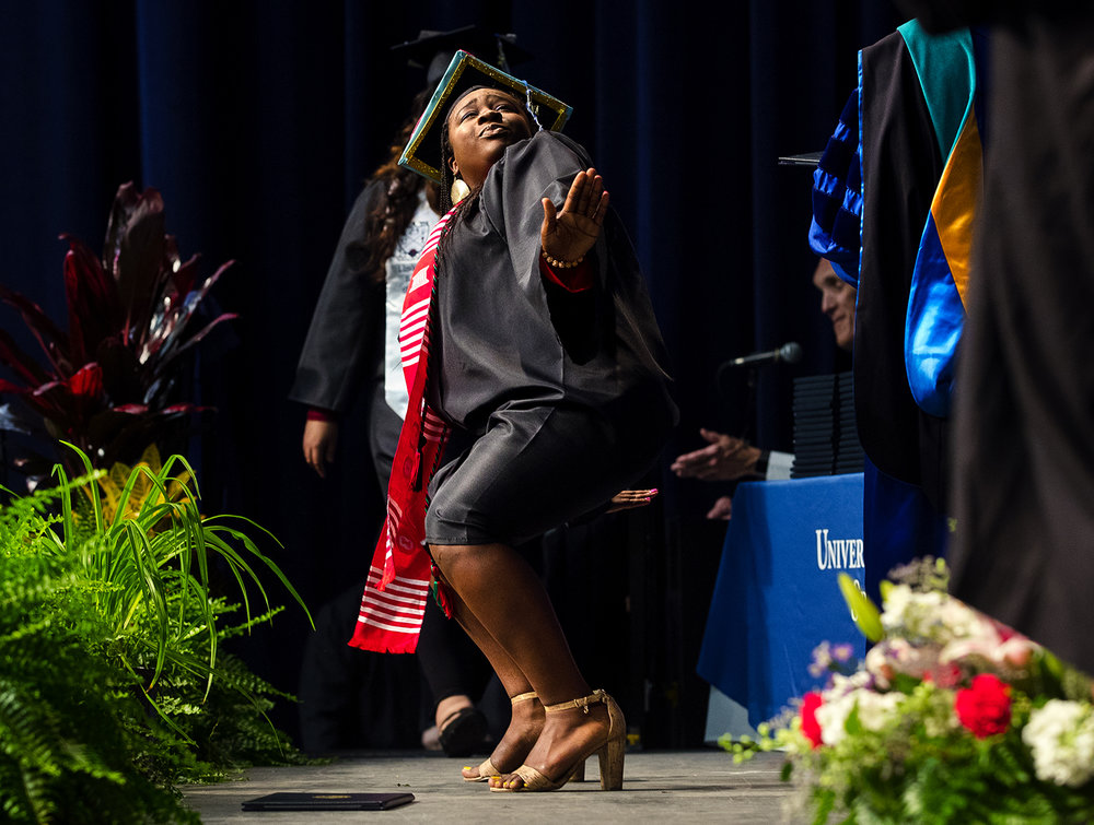 Taylor Dent strikes a pose as she walks across stage during commencement ceremonies for the College of Liberal Arts and Sciences at the Prairie Capital Convention Center Saturday, May 13, 2017. 