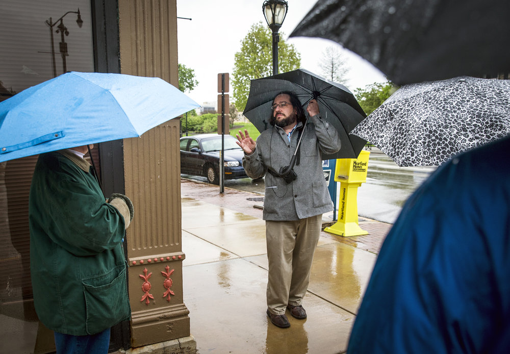 Anthony Rubano, of the Illinois Historic Preservation Agency, discuses the Horace Mann building while taking refuge under an umbrella from the rain along with the attendees to the first Downtown Springfield Incorporated Architectural Walking Tour of the year on the corner of East Washington Street and North 7th Street, Wednesday, May 3, 2017, in Springfield, Ill. The tours are free to attend and are held the first Wednesday of every month from May to October. [Justin L. Fowler/The State Journal-Register]