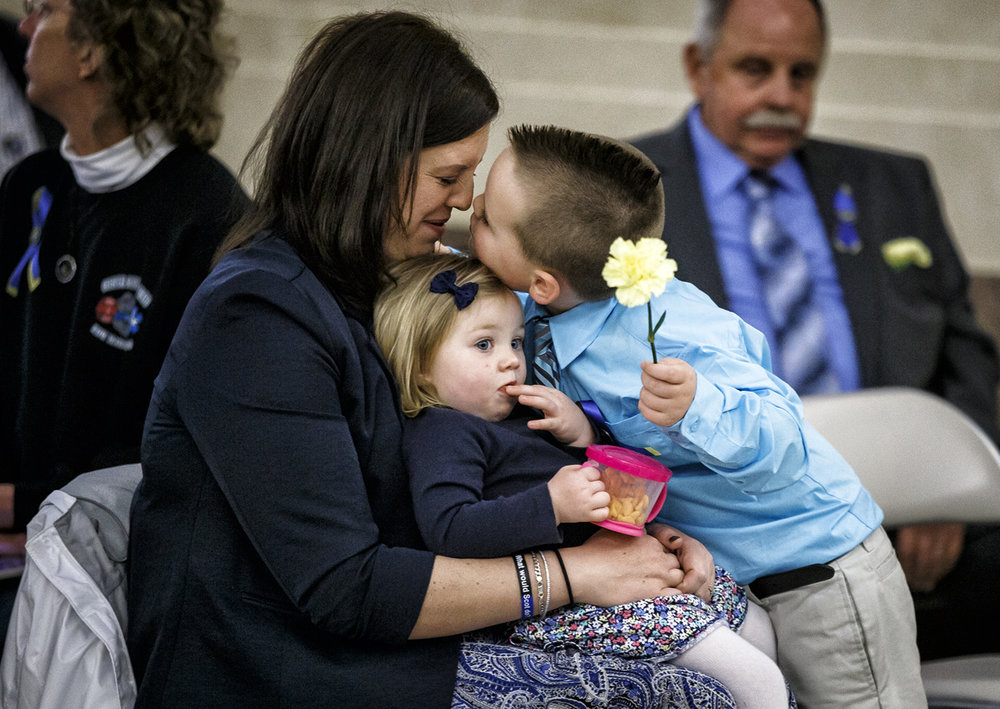 Officer Scot Fitzgerald's widow, Dani Fitzgerald, gets a kiss on the nose from her son, Colton, while holding her daughter Fynlee, as they wait for the ceremony to honor Fitzgerald during the 32nd annual Police Officers Memorial Day at the Illinois State Library, Thursday, May 4, 2017, in Springfield, Ill. Scot Fitzgerald was a police officer with the village of South Jacksonville and was killed in an automobile accident in March of 2016 while responding to a call on the highway. [Justin L. Fowler/The State Journal-Register]