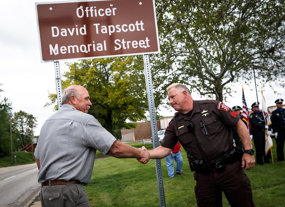 """Kenneth """"Tapper"""" Tapscott, left, and Sgt. Jim """"Tapper"""" Tapscott, right, with the Sangamon County SheriffÕs Department, shake hands after unveiling the new sign for their brother and uncle respectively, Officer David Tapscott, a Springfield police officer who died while responding to a disturbance call in 1979, during a ceremony at the intersection of North 9th Street and East Converse Street, Thursday, May 4, 2017, in Springfield, Ill. The roadway along North 9th Street was renamed Officer David Tapscott Memorial Street in honor of the fallen officer that passed away from the injuries suffered from a collision with the center support pylon of the railroad overpass on Christmas Eve in 1979. [Justin L. Fowler/The State Journal-Register]"""