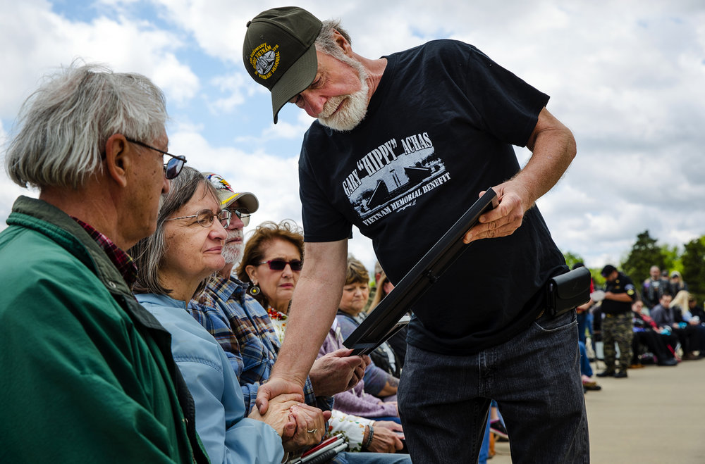 "Jim Mathes, the chair of the Illinois Vietnam Veteran's Memorial Vigil Committee, presents Barbara Aches Cherry a plaque in memory of her brother, Marine Lance Cpl. Robert ""Butch"" Achas, during the 29th annual Vietnam Veterans Memorial Vigil at the Illinois Vietnam Veterans Memorial at Oak Ridge Cemetery Saturday, May 6, 2017. Aches was killed by friendly fire in Vietnam March 14, 1965. [Ted Schurter/The State Journal-Register]"