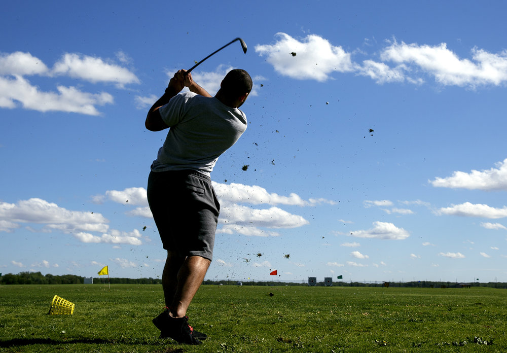 """Austin Bell watches his golf ball take flight at the Knight's Action Park hitting range Tuesday, May 2, 2017, where he was working his way through a bucket of balls with a friend, Wes Hunt. The pair admitted they were better at video games than they were at golf. """"We just play for fun,"""" Bell said. [Rich Saal/The State Journal-Register]"""