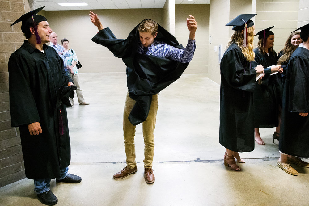 Steven Davis, left, watches as Kit Mefford hastily attempts to put on his graduation gown the wrong way before the Lincoln Land Community College commencement ceremony at the Prairie Capital Convention Center Friday, May 12, 2017. Roughly 300 of the 1,950 students eligible to graduate participated in the ceremony. [Ted Schurter/The State Journal-Register]