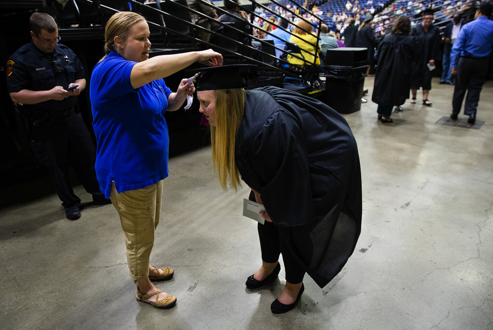 Sarah Scheufele adjusts the tassel on Kayla Smith's graduation cap before the Lincoln Land Community College commencement ceremony at the Prairie Capital Convention Center Friday, May 12, 2017.  [Ted Schurter/The State Journal-Register]
