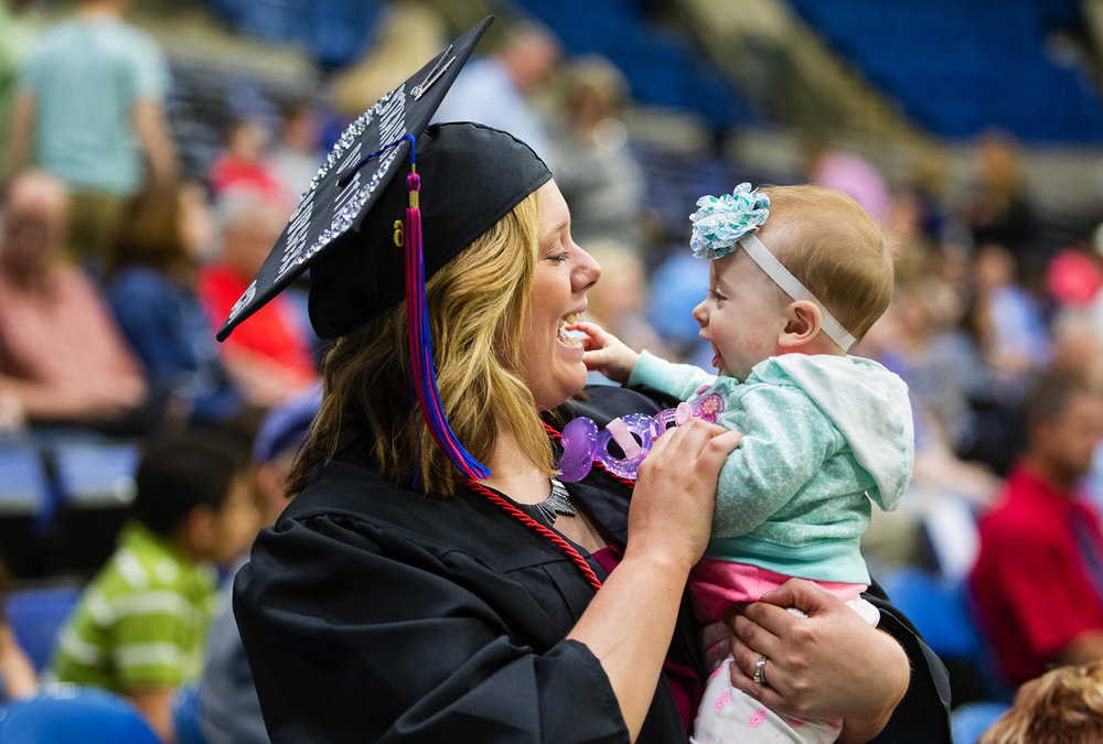 Chelsey Ayers holds her six-month-old niece Kenzlee Shanle before the Lincoln Land Community College commencement ceremony at the Prairie Capital Convention Center Friday, May 12, 2017. [Ted Schurter/The State Journal-Register]