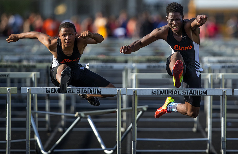 Lanphier's Cameron Smith, left, edges teammate Marvin Broomfield in the 110 meter hurdles during the 2017 2A Springfield Sectional at Memorial Stadium Thursday, May 18, 2017.  [Ted Schurter/The State Journal-Register]