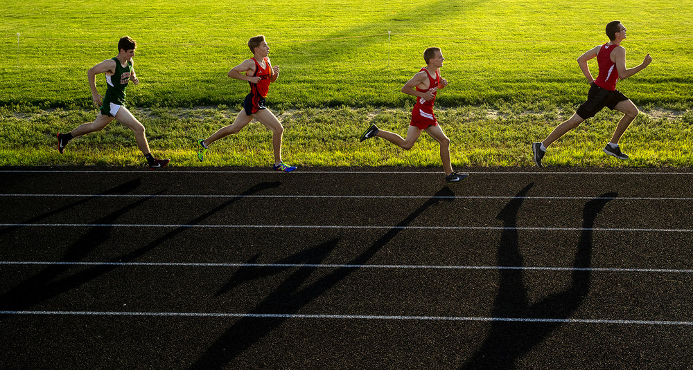 Runners in the 1600 meter run cast long shadows on the track during the 2017 2A Springfield Sectional at Memorial Stadium Thursday, May 18, 2017.  [Ted Schurter/The State Journal-Register]