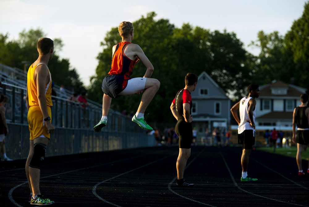 Rochester's Colton Mitchell leaps into the air as he waits for his lap during the 4x400 meter relay during the 2017 2A Springfield Sectional at Memorial Stadium Thursday, May 18, 2017.  [Ted Schurter/The State Journal-Register]