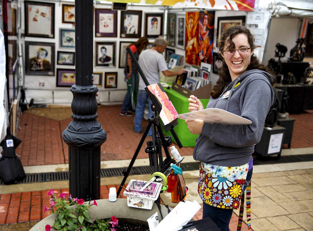 Kelsey Merkle, a mixed media artist from Clarence Center, N.Y. and first time exhibitor, works on a piece outside her booth at the Old Capitol Art Fair Saturday, May 20, 2017. [Rich Saal/The State Journal-Register]