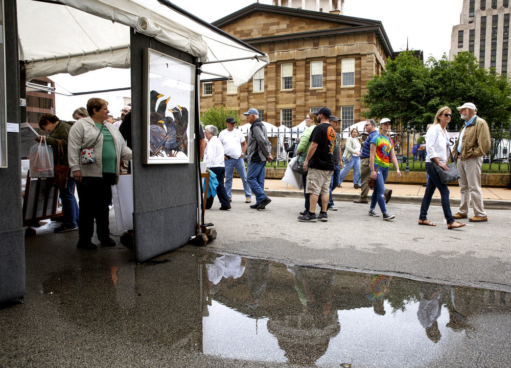 A rain shower early Saturday, May 20, 2017 left puddles in the street near the booth of Cleveland, Ohio artist Chuck Wimmer, but it had stopped in time for the start of the the Old Capitol Art Fair. [Rich Saal/The State Journal-Register]