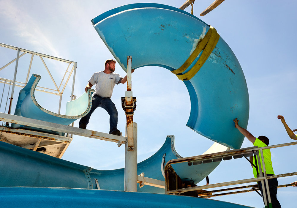 Springfield Park District employees Tim Wagoner, left, and Matt Evans guide a refurbished section of water slide into place at the Nelson Center Pool Monday, May 15, 2017. Two sections of the slide were re-fiberglassed. The side will be fully operational when the pool opens Memorial Day weekend. [Ted Schurter/The State Journal-Register]