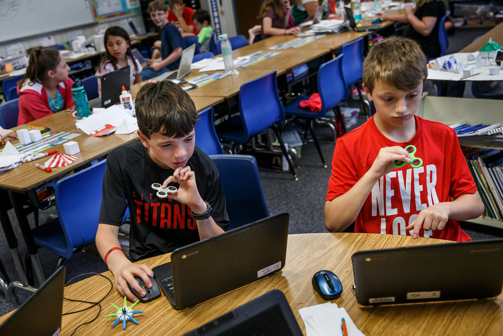 Luke Leahy, 11, left, and Cade McNeill, 11, right, work on a collaborative slide show report about the Great Chicago Fire while simultaneously using fidget spinners during class at Glenwood Intermediate School, Tuesday, May 16, 2017, in Chatham, Ill. The students are free to use the spinners as a way of helping them focus. [Justin L. Fowler/The State Journal-Register]