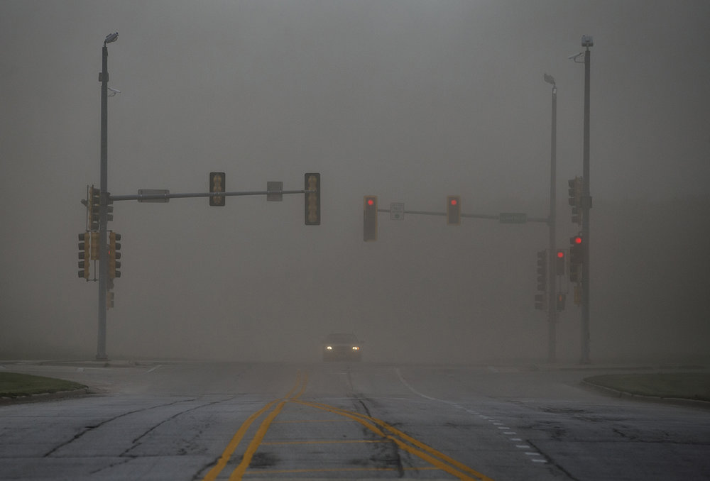 The headlights of a car shine through the intersection of IL-29 and Cardinal Hill Road as a dust storm blankets the area due to high winds, Wednesday, May 17, 2017, in Rochester, Ill. [Justin L. Fowler/The State Journal-Register]