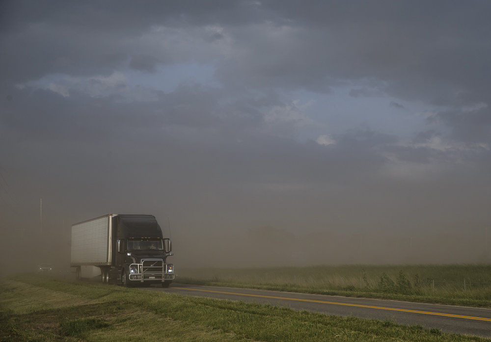 A tractor-trailer emerges from a cloud of dust along Hazel Dell Road parallel to a closed section of I-72 that was shut down as high winds kick up a dust storm, Wednesday, May 17, 2017, in Springfield, Ill. [Justin L. Fowler/The State Journal-Register]