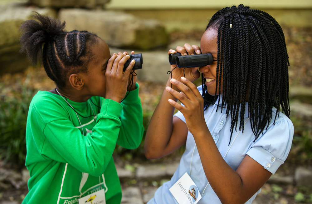 Takiya McCrary, left, and Jamylia Samuel peer at each other through binoculars they had just been given for their hike at The Adams Wildlife Sanctuary Thursday, May 18, 2017. The girls, students at St. Patrick Catholic School, and their classmates were participating in a six week program called The Bird Detective where they learn about birds and their habitat. Federal funding for the program was on the chopping block before it was restored. [Ted Schurter/The State Journal-Register]