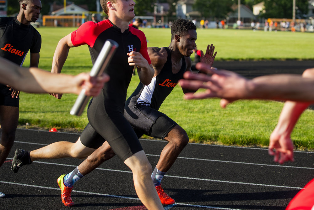 Lanphier's Marvin Broomfield takes off after getting the baton from Perrion Bolden in the 4x200 meter relay during the 2017 2A Springfield Sectional at Memorial Stadium Thursday, May 18, 2017.  [Ted Schurter/The State Journal-Register]