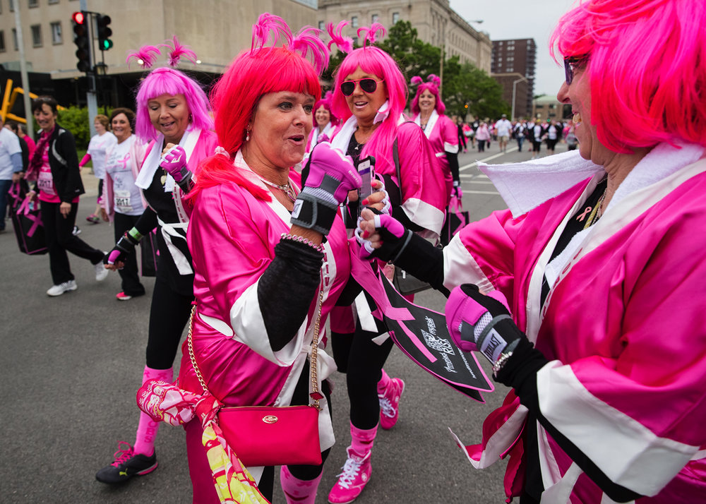 Members of the Pinkalicious Bullets playfully duke it out as they participate in the 2017 Komen Springfield Race for the Cure Friday, May 19, 2017. [Ted Schurter/The State Journal-Register]