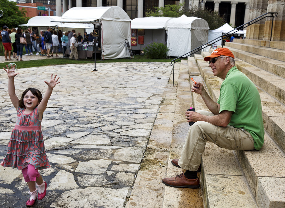 Evelyn Havey chases bubbles her dad Jim Havey had blown while the two took a short break from the Old Capitol Art Fair Saturday, May 20, 2017. [Rich Saal/The State Journal-Register]
