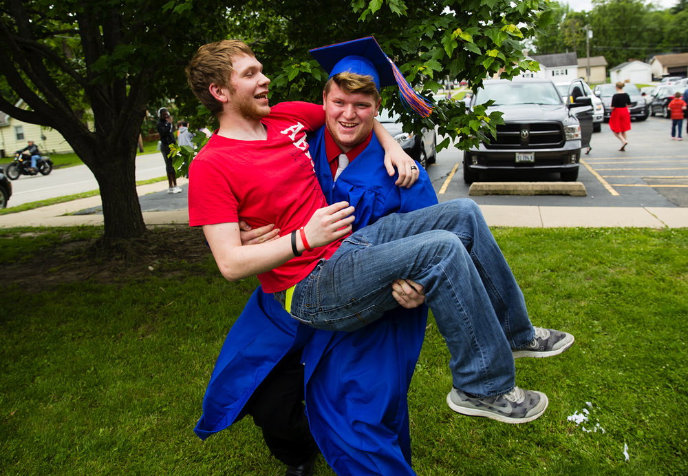 Matthew Bell lifts his cousin Anthony Gleason while taking family photos after the Riverton High School commencement service Sunday, May 21, 2017. [Ted Schurter/The State Journal-Register]