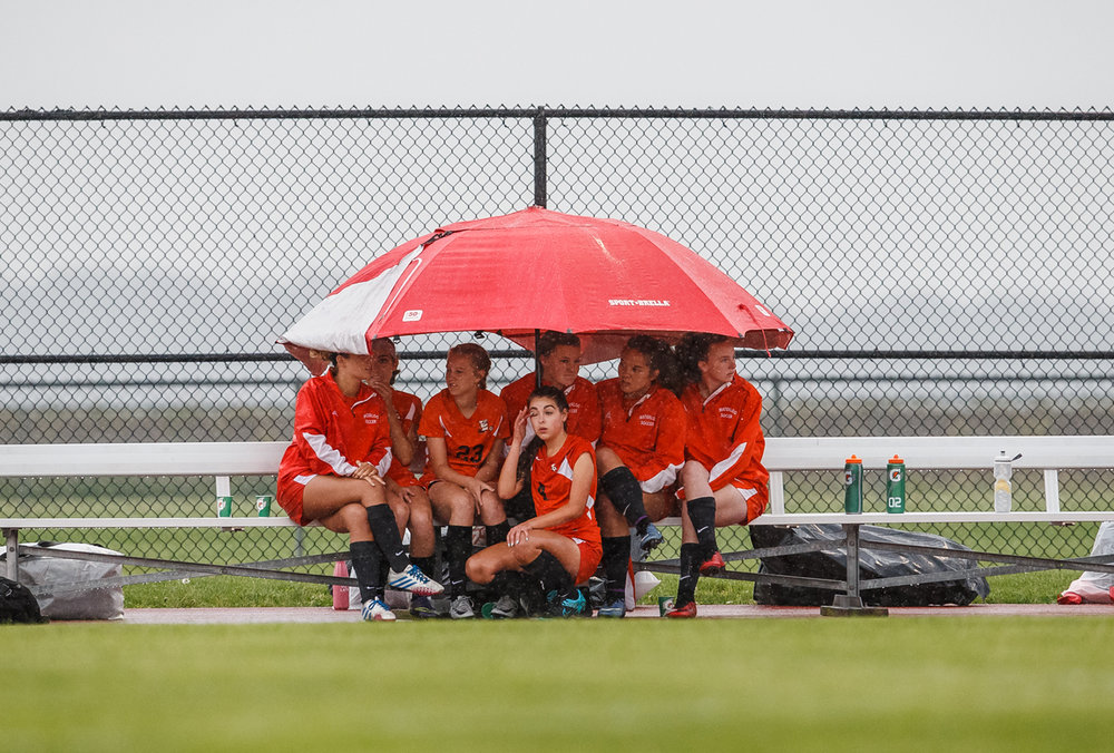 The Waterloo bench huddles underneath an umbrella as the rain begins as they take on Glenwood in the first half during the Class 2A Glenwood Sectional at Glenwood High School, Tuesday, May 23, 2017, in Chatham, Ill. [Justin L. Fowler/The State Journal-Register]