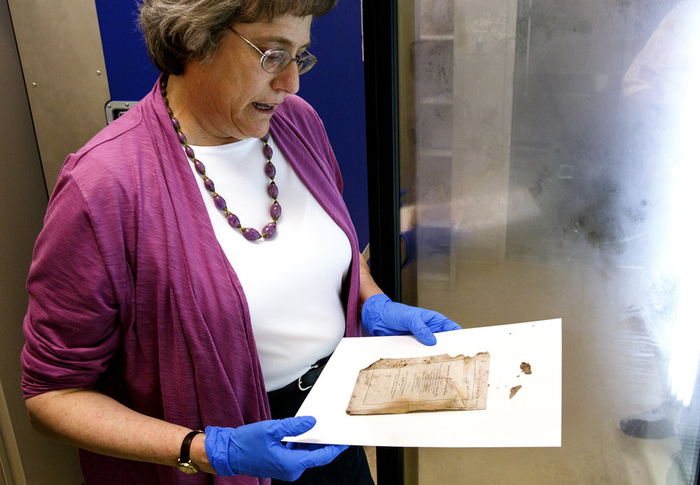 Bonnnie Parr, historical document conservator at the Abraham Lincoln Presidential Library, holds a page from the dedication in 1912 of the Springfield YWCA Tuesday, May 16, 2017 at the Abraham Lincoln Presidential Library.  The document was among several found inside a time capsule, which had been sealed in the building's cornerstone. The stone and the capsule were recovered before the building was razed in March. [Rich Saal/The State Journal-Register]