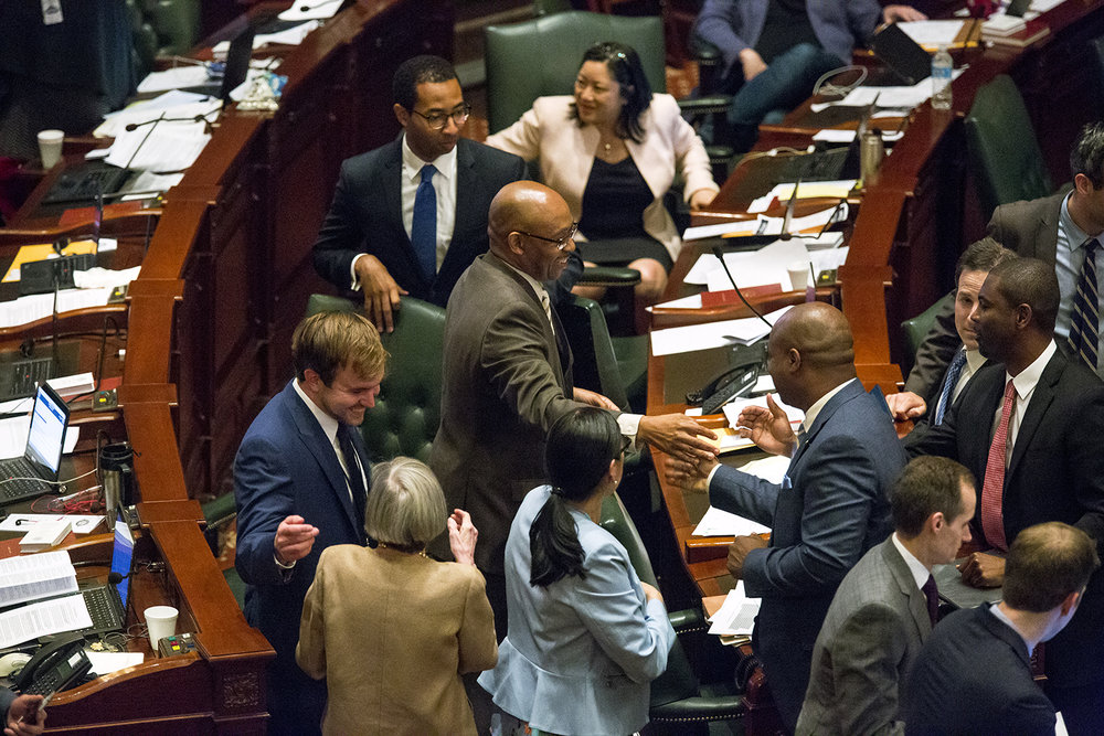 Rep. William Davis, D-Homewood, is congratulated by colleagues after his school funding overhaul bill passed in the House Wednesday, May 31, 2017 at the Capitol. [Rich Saal/The State Journal-Register]