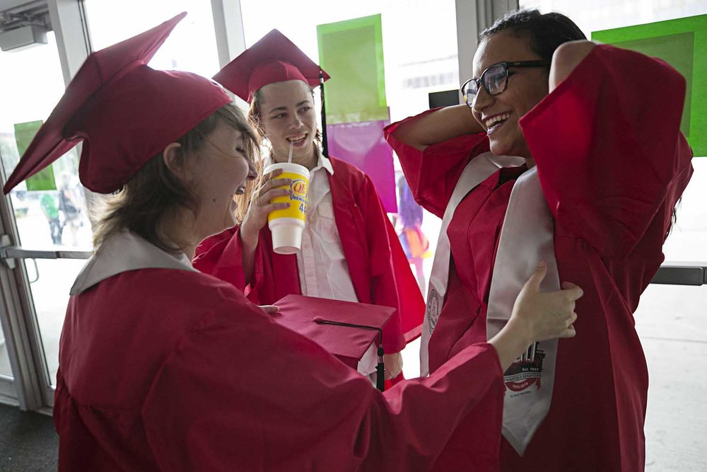 Lisa Rexroad, left, Dakota Knox, and Lyric Bernal help each other get ready before the Springfield High School graduation at the Bank of Springfield Center Saturday June 3, 2017 [Photo by Jason Johnson]
