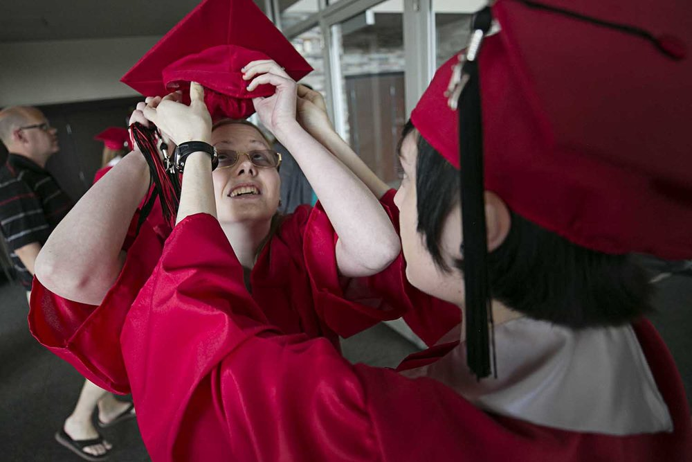 Hailey Moore helps Jasmine Gaspardo with her mortarboard before the Springfield High School graduation at the Bank of Springfield Center Saturday June 3, 2017 [Photo by Jason Johnson]