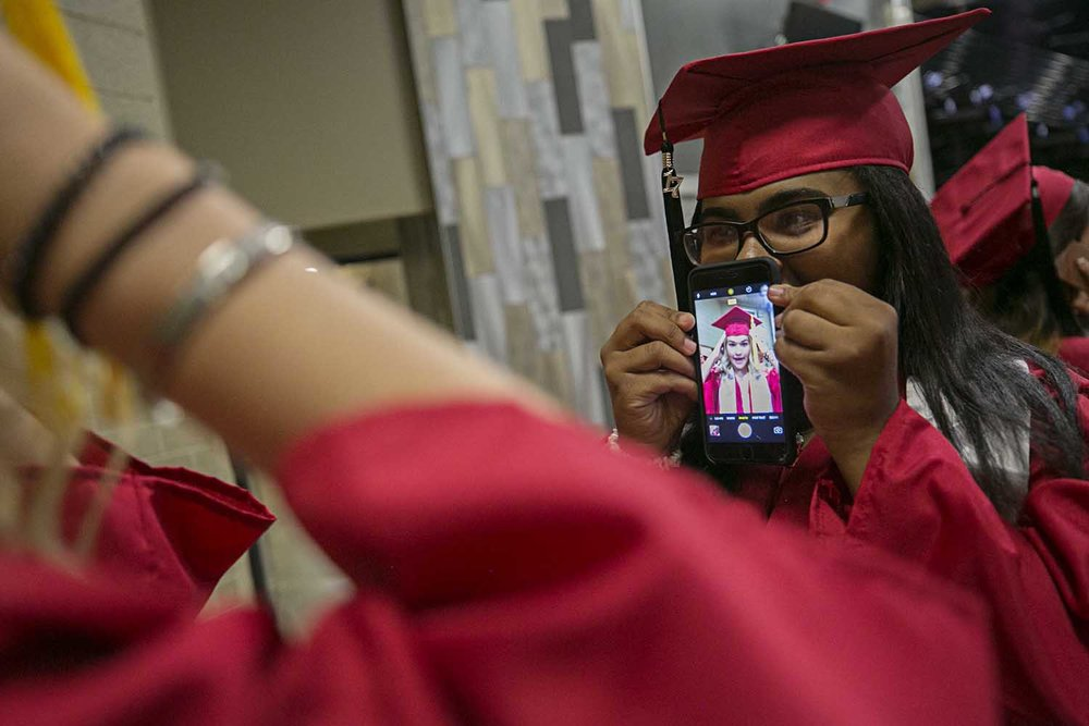 Jailynn Brown holds a phone for Jenna Milward as she gets her mortarboard straight before the Springfield High School graduation at the Bank of Springfield Center Saturday June 3, 2017 [Photo by Jason Johnson]